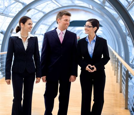 Satisfied and happy business people walking on modern office corridor. Stock Photo