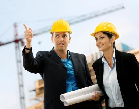 competencias laborales: Los j�venes arquitectos que llevaba un casco protector de pie delante de una obra de construcci�n.  Foto de archivo
