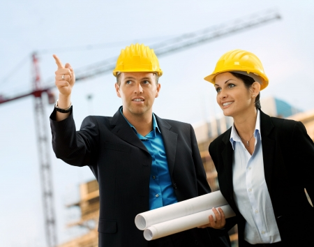 Young architects wearing a protective helmet standing in front of a building site. Stock Photo - 1738692
