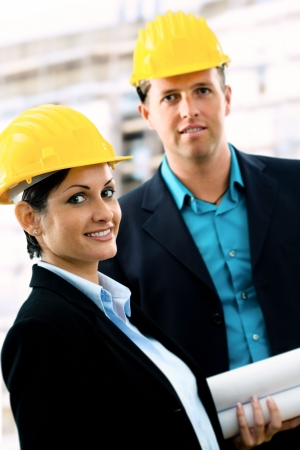 Young architects wearing a protective helmet standing in front of a building site. Stock Photo - 1738688