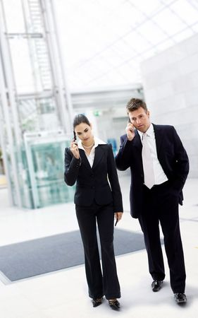 Busy business people walking and calling on mobile. Imagens