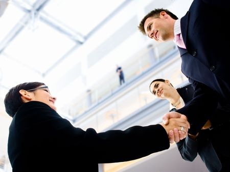 Business people shaking hands in the entrance hall of the office building. Selective focus is placed on the hands. photo