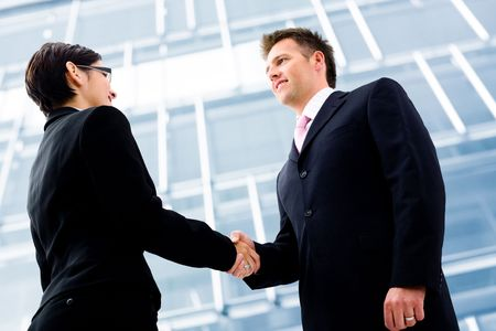 placed: Business people shaking hands in front of an office building. Selective focus is placed on the hands. Stock Photo