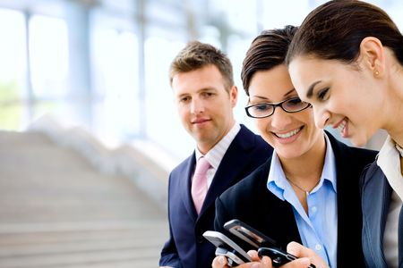 Young businesswomen sharing info on mobile phones. Selective focus is placed on the woman in the middle. Stock Photo