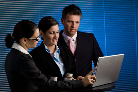 placed: Young business people working on laptop at late night. Selective focus is placed on the woman in the middle. Stock Photo