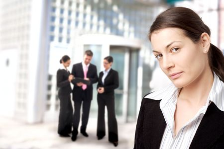 buiding: Young businesswoman standing in front of an office building.