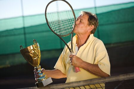 Active senior man in his 70s is very thankful to his tennis racklet while holding a cup in hand. Outdoor, sunlight. photo