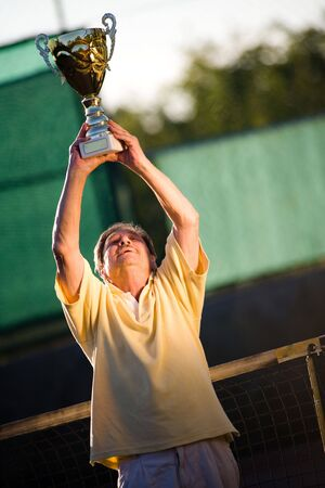 Active senior man in his 70s is posing on the tennis court with cup in hands. Outdoor, sunlight. photo