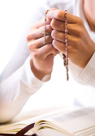 Christian believer praying to God with rosary in hand. Vertical version.