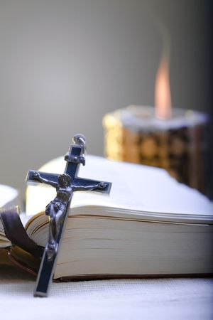thankfulness: Old Cross and the Holy Bible laying on the table in fornt of a lighting candle.