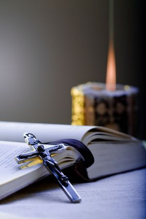 piety: Old Cross and the Holy Bible laying on the table in fornt of a lighting candle.