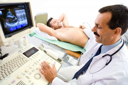ultrasound scan: Doctor performing an ultrasound scan on young male patient. Real people, real locacion, real image on the screen, not a staged photo with models.