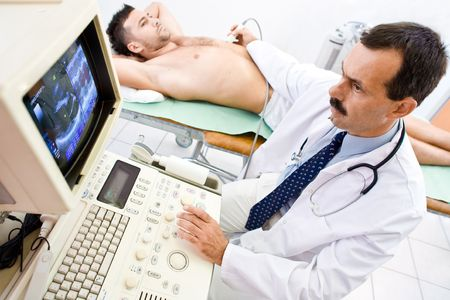 ultrasound: Doctor performing an ultrasound scan on young male patient. Real people, real locacion, real image on the screen, not a staged photo with models.