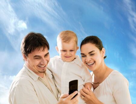 Happy family looking at mobile phone sceen outdoor.