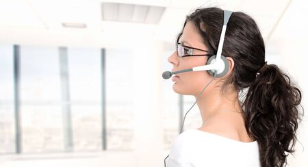 Pretty young woman works as a helpdesk operator. Stock Photo - 1989300