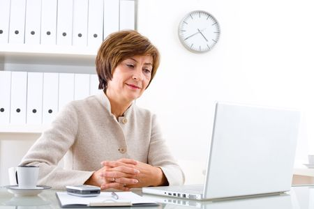 Senior businesswoman sitting at desk in office, looking at screen.
