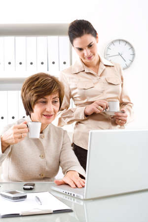 Senior businesswoman and young assistant working  at desk in office, smiling and drinking coffee. photo