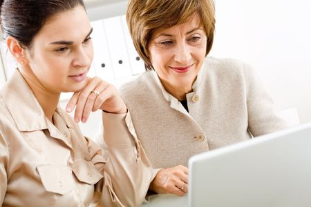 Businesswomen looking at laptop screen together, smiling. Stock Photo - 2021616