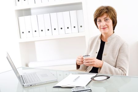 Senior businesswoman working at desk in office, looking at camera, smiling. photo