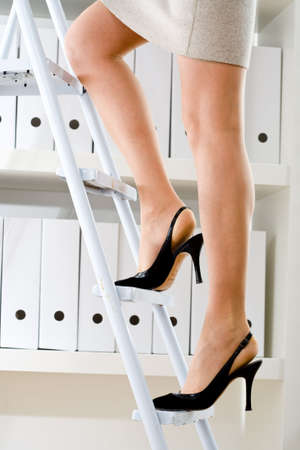 Businesswoman climbing on ladder to seek files on shelf. Stock Photo - 2025354