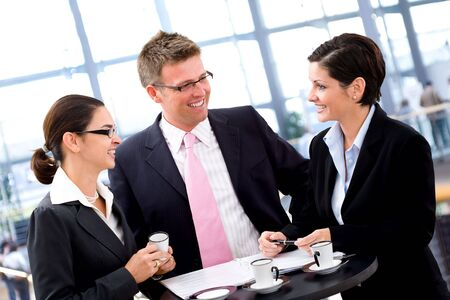 Business people having meeting by the coffee table, smiling. photo