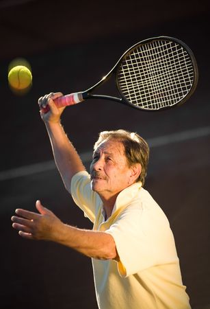 Active senior man in his 70s is playing tennis.  photo