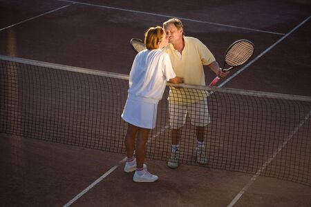 Active senior couple is shaking hands on the tennis court with tennis rackets in hand. Outdoor, sunlight. photo
