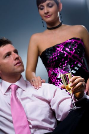Couple drinking champagne on a party. Selectvie focus placed on the glass. photo