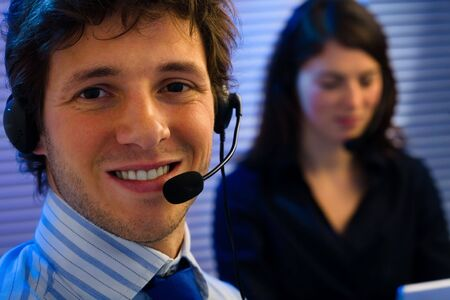 telecommuting: Male and female customer service representative working in office, smiling. Stock Photo