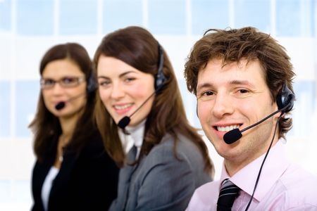 telework: Customer service team working in headsets, smiling.