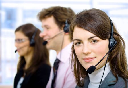 Customer service team working in headsets, smiling. photo