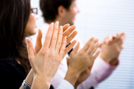 aplaudiendo: Los ejecutivos sentados en una fila y aplaudiendo. Primer plano de las manos.  Foto de archivo