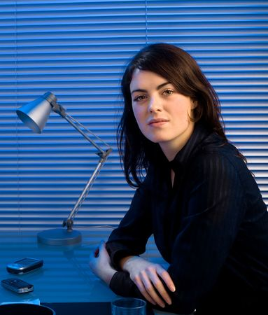 late twenties: Young caucasian businesswoman working late at office and posing for portrait.