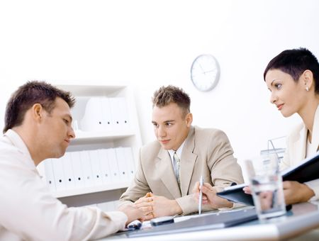 Businesspeople conducting job interview in brightly lit office. photo