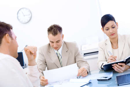 JOB INTERVIEW: Businesspeople conducting job interview in brightly lit office.