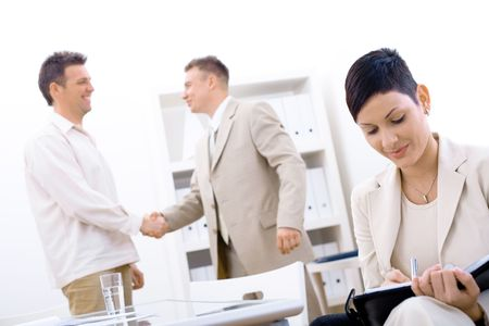 businessmeeting: Businessteam of three working at office, businesswoman sitting in foreground, making notes, smiling, businessmen shaking hands in background.