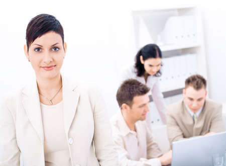 businessmeeting: Businesswoman standing in front looking at camera, smiling. Three business colleagues working on laptop computer in background.