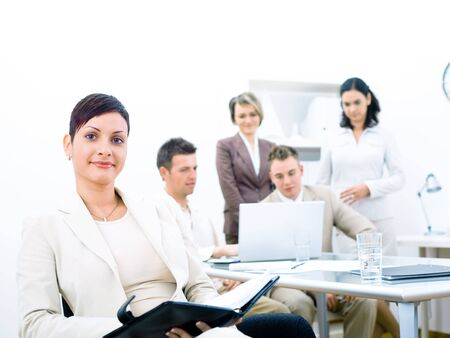 Group of five young business people working at office with businesswoman sitting in front.