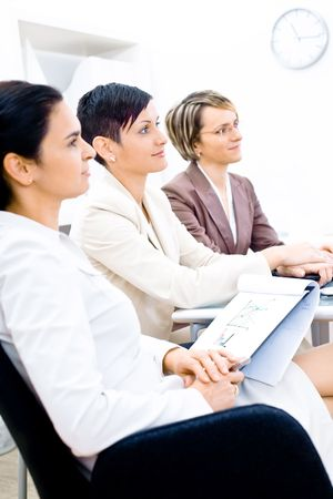 Three businesswoman attending on business training. Sitting in a row, making notes, smiling. photo