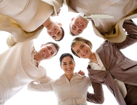 ange: Small group of business people standing in huddle, smiling, low ange view. Stock Photo