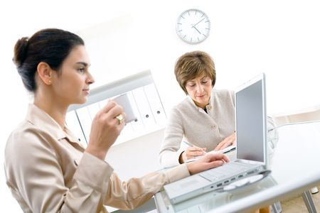 Senior businesswoman and young assistant working  in office. photo