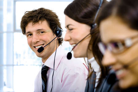 Customer service team working in headsets. Focus placed on smiling man in back. Stock Photo - 2383430