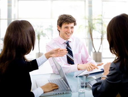 Three young businespeople working in team at office, smiling. Stock Photo