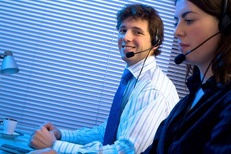 sales call: Customer service team working in headsets, late night at office. Focus placed on smiling man in back.