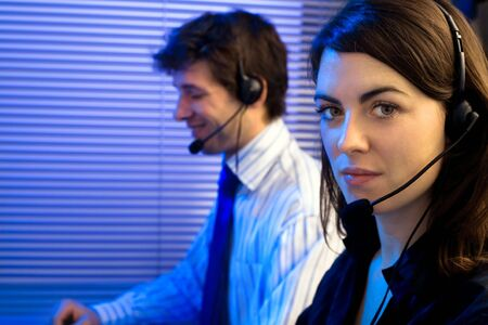 sales call: Customer service team working in headsets, late night at office. Focus placed on woman in front.