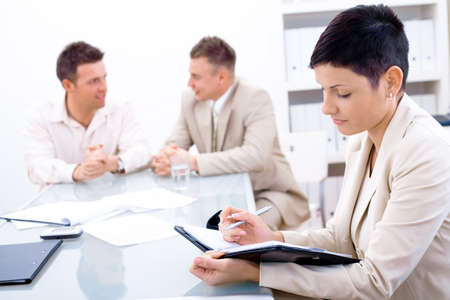 Businessteam of three working at office, businesswoman sitting in foreground, making notes. Stock Photo - 2383416