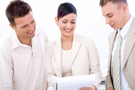 Three young business people wearing light business outfit looking at document and smiling. Stock Photo