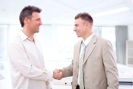 businesswear: Two businessmen shaking hands in office, smiling.