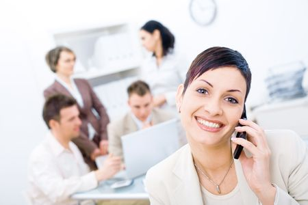 Businesswoman sitting in front, calling on phone, looking at camera, smiling. Four business colleagues working on laptop computer in background. Stock Photo