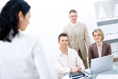 businessmeeting: Four business people working in office. Three working together on laptop and looking up and smiing to fourth colleague.  Stock Photo